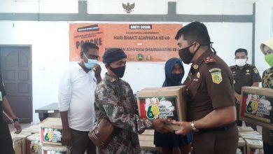 Kepala Kejaksaan Negeri Karimun, Rahmat Azhar SH MH, memberikan secara simbolis paket sembako pada salah seorang warga di kantor Desa Pangke (yan)
